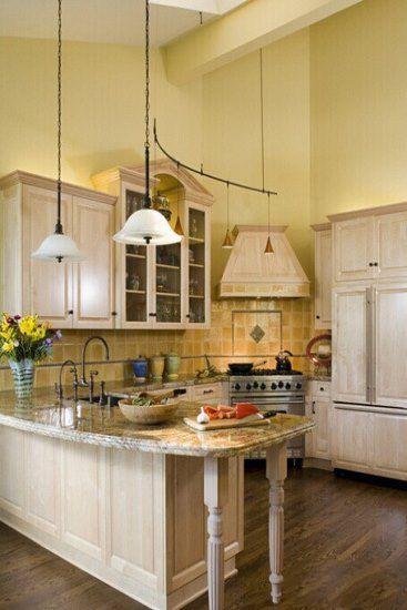 鹅黄色的墙面下,淡橙色瓷砖拼贴而成的厨房背景墙与米白色欧式橱柜图片