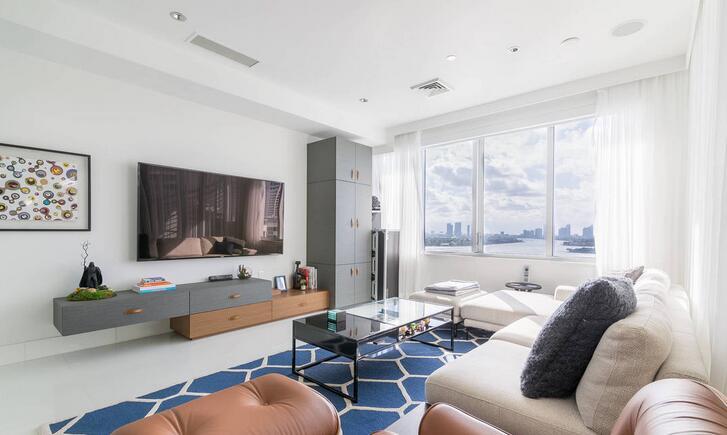 平房客厅装修图片案例 平房客厅装修以其简约优雅的时尚美感吸引人的眼球,整个房间的地面铺设着原木风情的瓷砖拼贴地板,灰白色的墙壁天花板连为一体,奠定了整个房间淡雅清新的基调。房间中间灰白色的布艺组合式沙发环绕着木制方形茶几,造型时尚夸张的电视背景墙带给人独具美感的视觉体验,墙壁上现代风格的挂画与天花板地板连为一体和整个房间的搭配相协调一致,让人过目不忘。