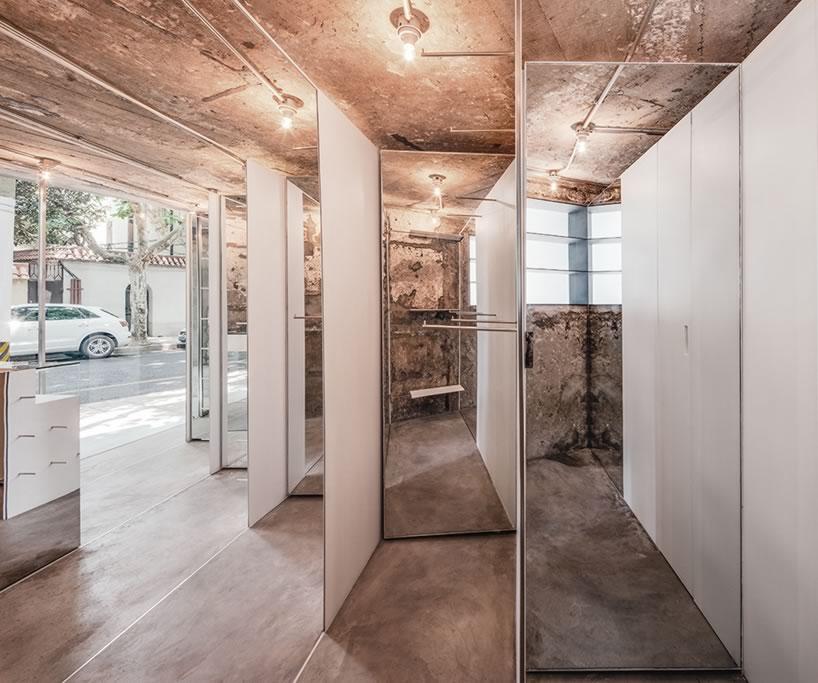 夜景效果   展示架中每两个薄板之间的空间都安装有镜子,能够反映出粗粝的墙面并彰显了展示架的纤薄。最后,室内最大的空间都用作试衣间,而所有试衣间的后面均可作为储藏空间。高度反光的收银台面延续了室内表面用材质感。ALL SH室内色调简单的镜子、白色金属、不锈钢与建筑结构中混凝土的粗糙原生态形成鲜明对比,令20平方米大小的室内空间看起来要比其真实面积更大一些。