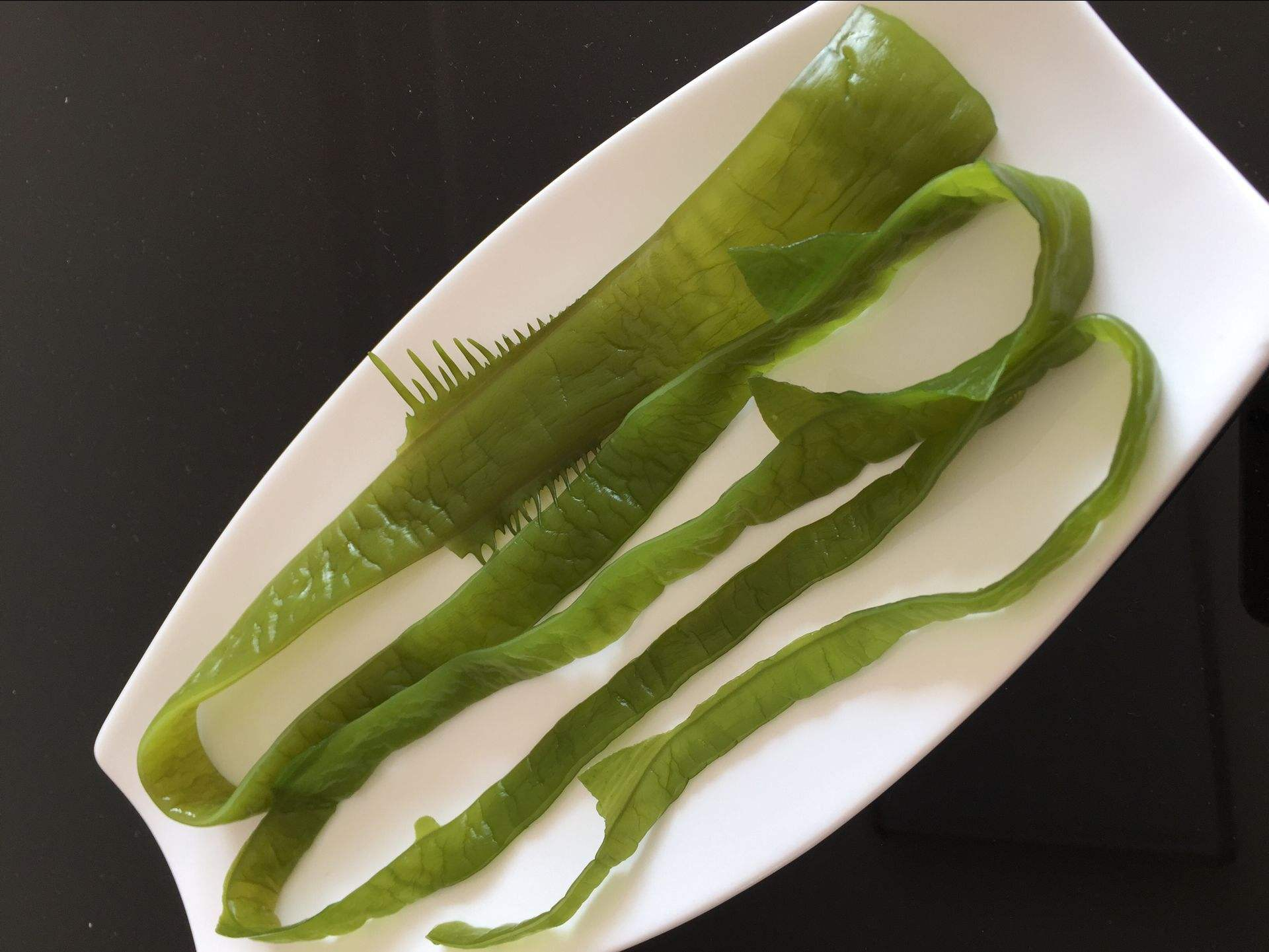 海白菜的细胞呈现多角形,叶绿体片状。其为两层细胞组成的膜状体,高大约10-30CM。在海白菜的基部没有柄,有像盘状的用于固定的触角,其是由基部两层细胞间向下延伸而出的。其繁殖方式可以无性生殖也可有性生殖,孢子体与配子体形世代交替。其主要生活于中、低潮间带岩石上或石沼中。在我们中国,主要以东海、南海较为常见,其果肉可食用也可作饵料。   海白菜和海带的区别   1、海白菜学名石莼,为藻类植物科孔石莼的藻体,又名海菠菜、海莴苣、海条、青苔菜、裙带菜等。藻体碧绿色,单独或丛生,高1014 厘米,形体常有