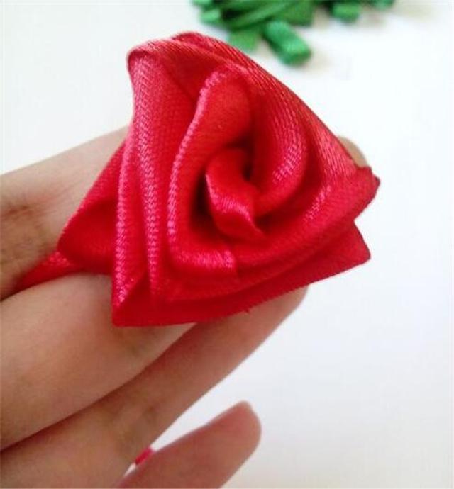 玫瑰花的折法有很多种,你可以用纸折玫瑰花,用布折玫瑰花,用彩带折玫瑰花。前两种在网上的教程已经很多了,今天小编要教大家的则是彩带玫瑰花的折法,一起看看的彩带玫瑰花的折法图解吧。   彩带玫瑰花的折法一   彩带玫瑰花的折法材料:彩带,一般一卷可以折一束玫瑰花。    方法步骤:   1、把彩带留下花柄长度地方成90度角对折。   2、彩带绕着花柄卷半圈,再绕着花柄卷半圈,从而绕成了一朵玫瑰花。   3、然后继续绕着。   4、把彩带和花柄重叠,用绳子扎在一起成为束玫瑰花,是不是很好看呢?