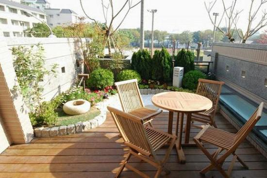 弧形的花园盆景设计,木质的小型桌椅更是让居室阳台别有一番风味!图片